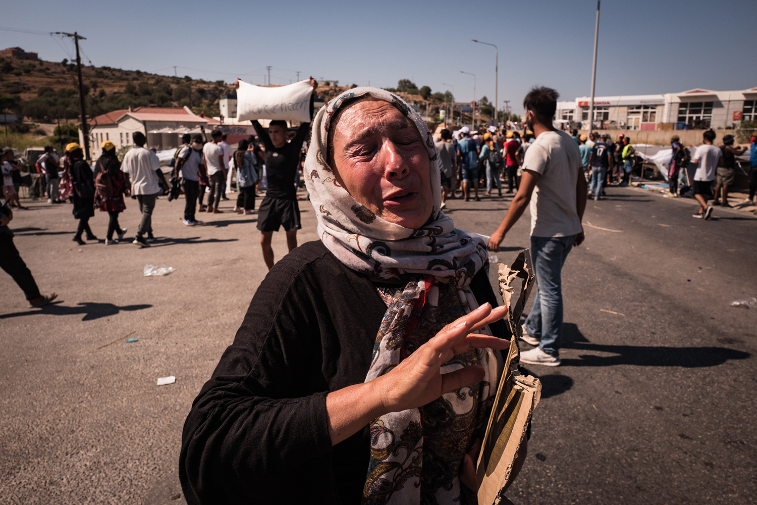 A refugee woman cries during a protest in the main street connecting Moria to Mytilene, Lesbos, on Sept. 12, reacting to plans to move refugees to a new camp.