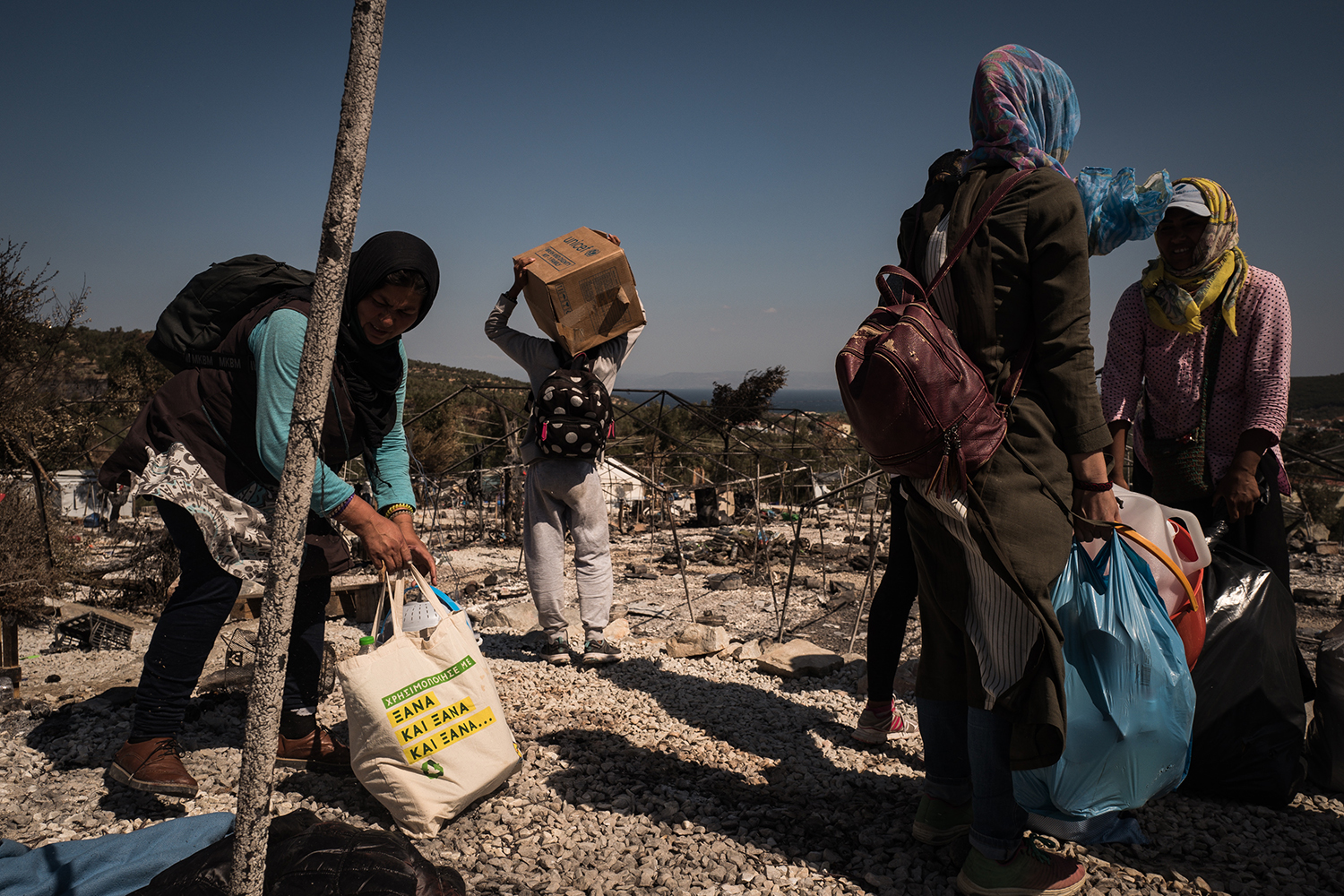 Afghan women collect their belongings from the Moria camp to bring to the new Kara Tepe facility on Sept. 14.