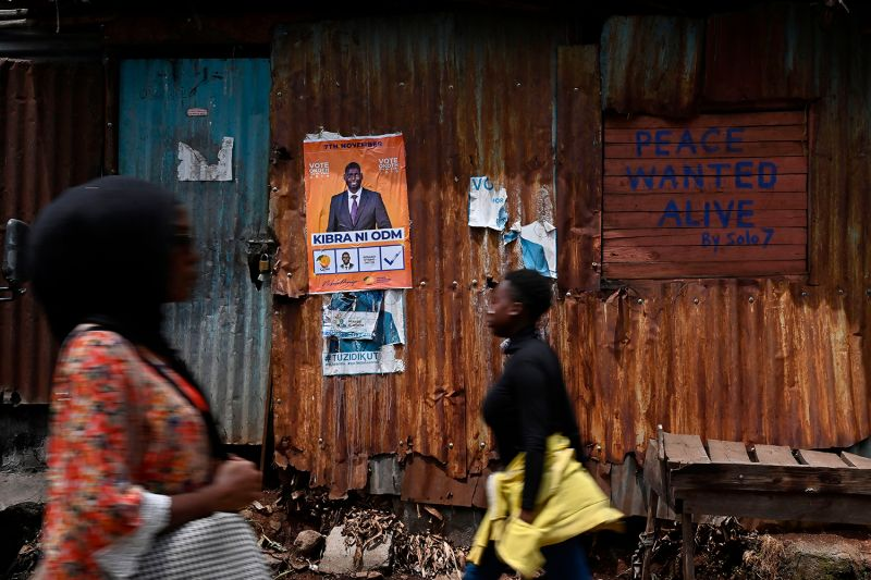 People walk past graffiti calling for peace in Nairobi
