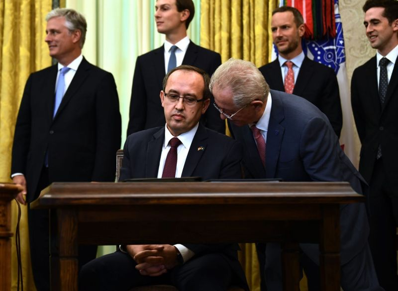 Kosovar Prime Minister Avdullah Hoti speaks with an aide after signing an agreement on opening economic relations with Serbian President Aleksandar Vucic in the White House on Sept. 4.