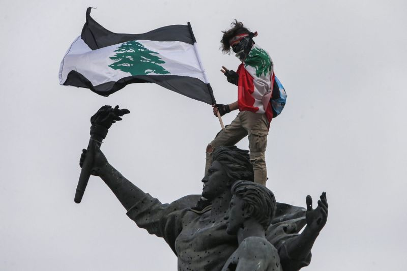 A demonstrator holding a Lebanese flag