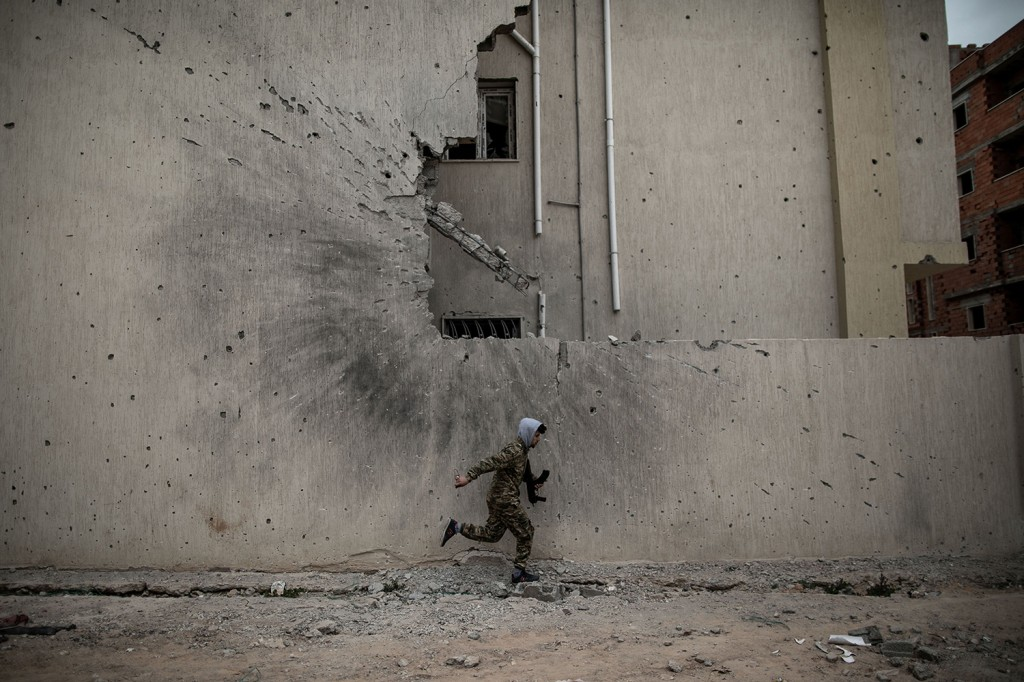A soldier runs for cover in Libya.