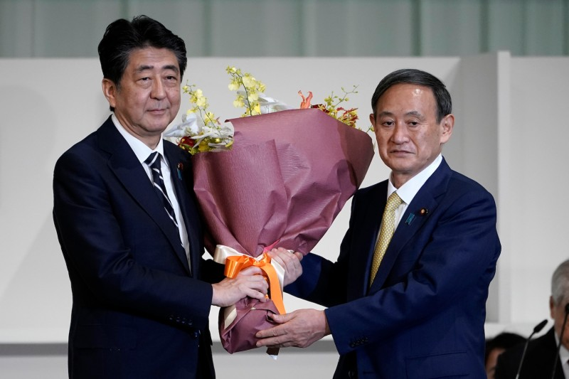 Incoming Japanese Prime Minister Yoshihide Suga accepts flowers from his predecessor, Shinzo Abe, after winning the leadership election of the Liberal Democratic Party.
