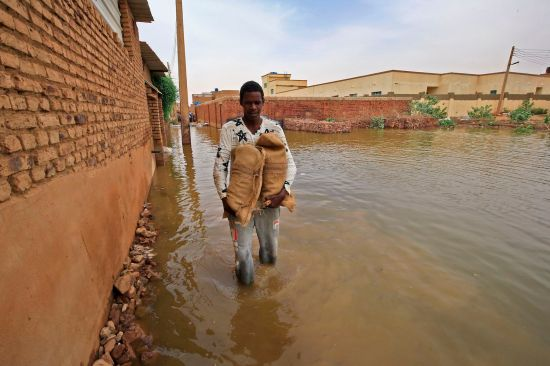 A Sudanese man holds bags to build a barricade amid flood waters in Tuti island, where the Blue and White Nile merge between the twin cities of Khartoum and Omdurman, on Sept. 3.