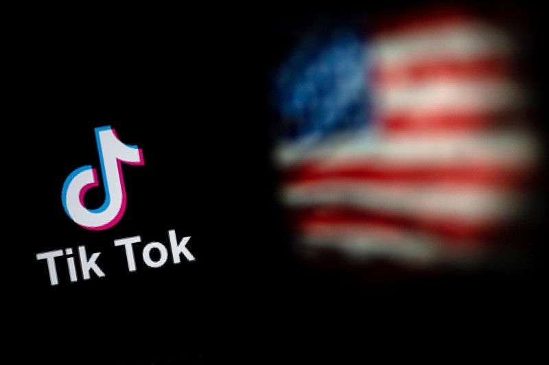This photo illustration taken shows the logo of the social network app TikTok and a U.S. flag on the screens of two laptops.