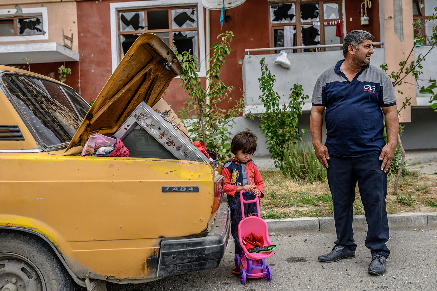 A man stands with his child by a car outside a damaged apartment building in Terter, Azerbaijan, after the family took their last belongings from their flat during a ceasefire between Armenia and Azerbaijan on Oct. 10. BULENT KILIC/AFP via Getty Images)