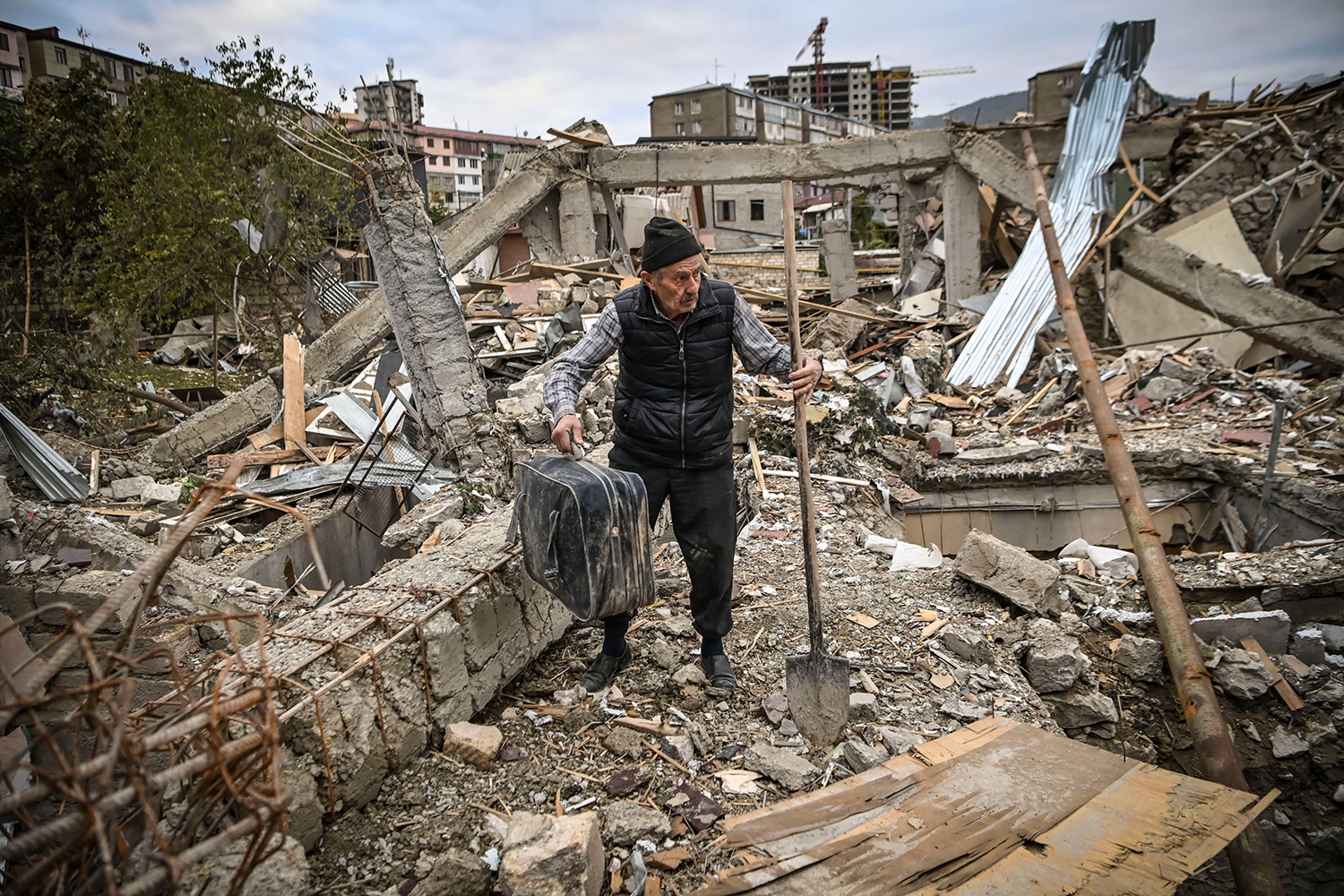 Retired police officer Genadiy Avanesyan, 73, searches for his belongings in the remains of his house, which was destroyed by Azeri shelling, in the city of Stepanakert, Artsakh, on Oct. 10. Amenia and Azerbaijan traded accusations of new attacks that day in breach of a ceasefire deal to halt weeks of fierce fighting over the disputed Nagorno-Karabakh region. ARIS MESSINIS/AFP via Getty Images
