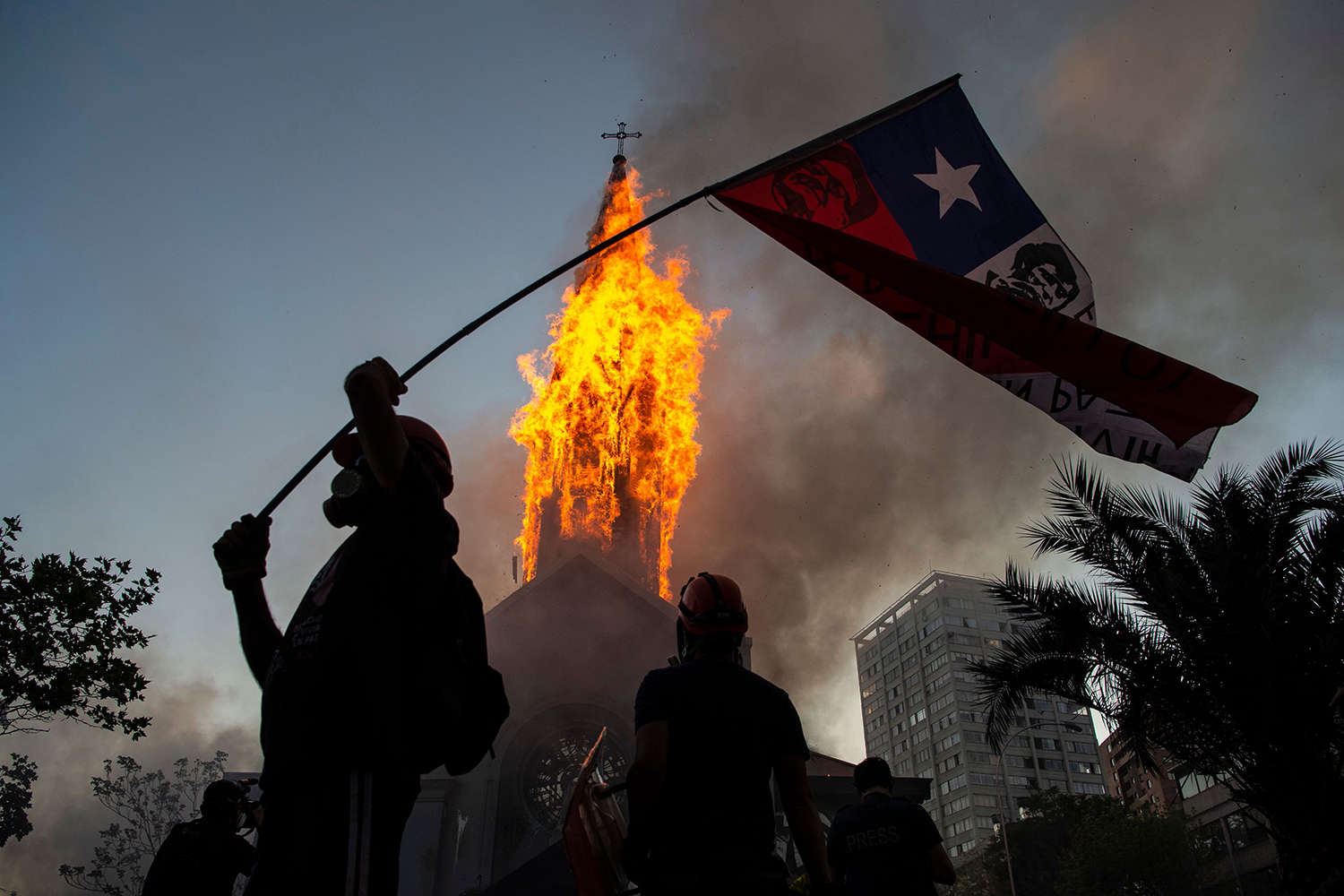 A church burns as demonstrators gather in Santiago on Oct. 18 to mark the first anniversary of the social uprising in Chile. The demonstration was held a week before Chileans successfully voted in a referendum to rewrite the dictatorship-era constitution—one of the key demands when the protest movement began a year ago. MARTIN BERNETTI/AFP via Getty Images