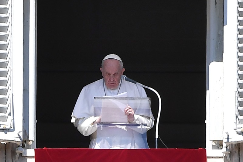 Pope Francis prays as he addresses the crowd from the window of the apostolic palace overlooking St. Peter's Square during his Angelus prayer at the Vatican on Oct. 18.