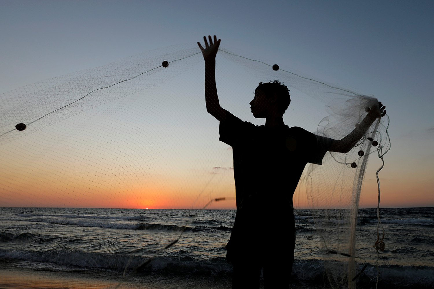 A Palestinian fisherman repairs his net at a beach in the northern Gaza Strip on Oct. 5. Suhaib Salem/REUTERS