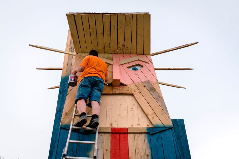 A man works on a wooden statue made to resemble US President Donald Trump in the village of Sela pri Kamniku, about 20 miles northeast of Ljubljana in Slovenia, the home country of Trump's wife on August 28, 2019.