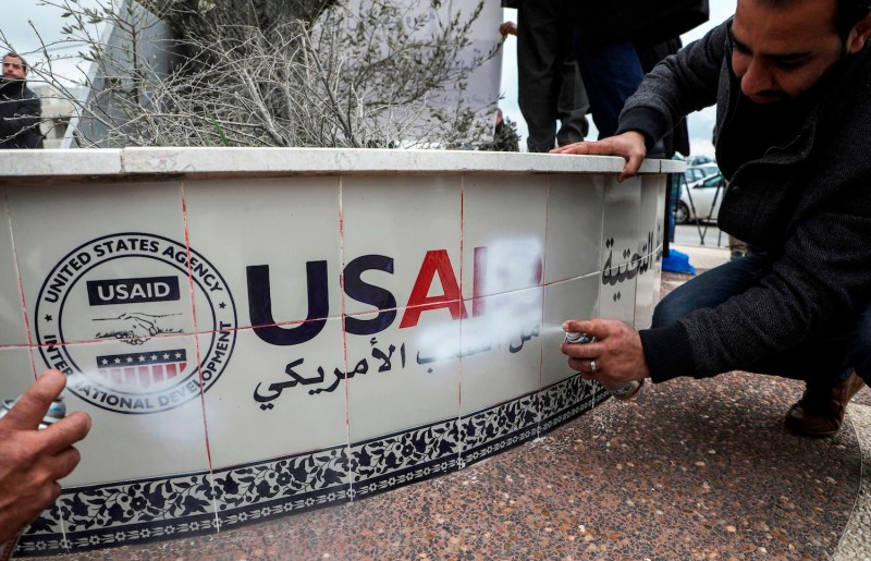 Palestinian protesters spray paint to cover the logo of the United States Agency for International Development (USAID)