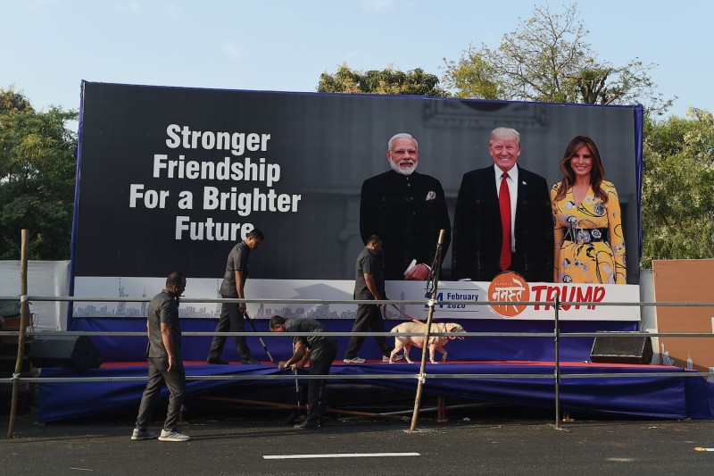 Officials with a sniffer dog inspect a stage displaying pictures of India's Prime Minister Narendra Modi, U.S. President Donald Trump, and first lady Melania Trump, on the outskirts of Ahmedabad, India, on Feb. 23.