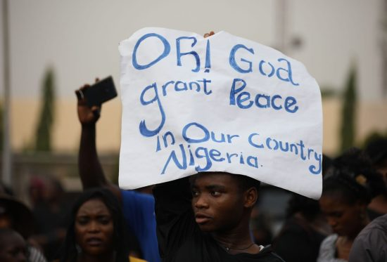 Christians hold signs as they march on the streets of Abuja, Nigeria.