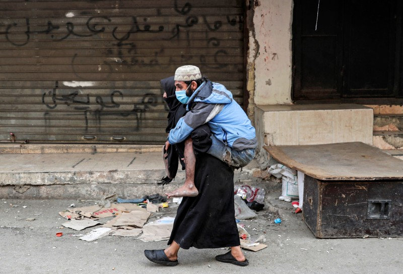 A woman carries a diabled man wearing a protective face mask the Sabra neighbourhood of Beirut where many Palestinian refugees still live, amid measures coordinated with Palestinian security forces to shut down all shops in a bid to limit the spread of COVID-19 coronavirus disease, on March 22, 2020.