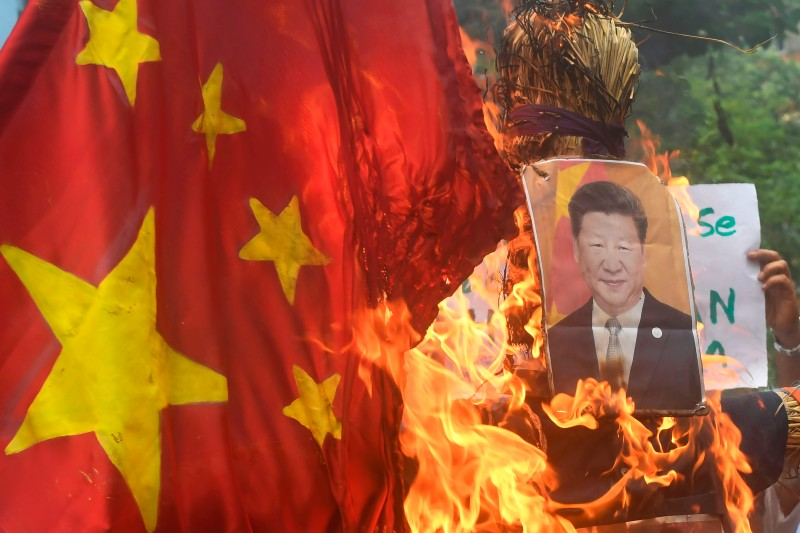 Indian protesters burn an effigy of Chinese President Xi Jinping and a Chinese flag during an anti-China demonstration in Kolkata on June 18.