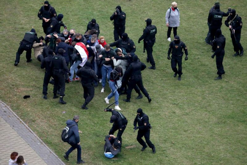 Riot police detain protesters at a march in Belarus on Oct. 11.