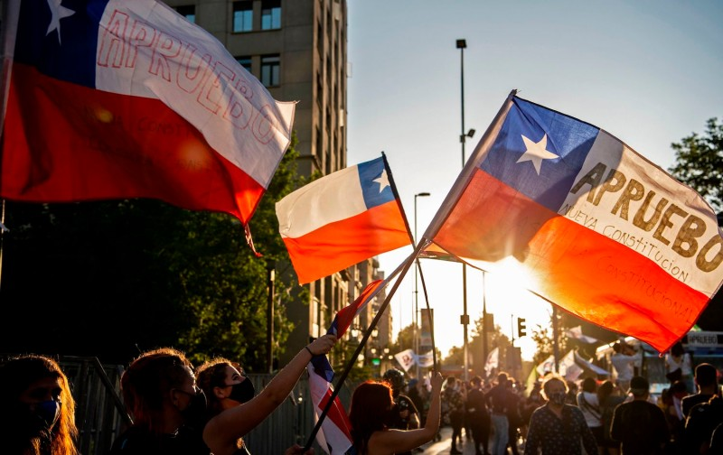 People with Chilean flags take part in a rally ahead of Sunday's referendum, in Santiago, on Oct. 22. Chileans will be asked two questions: if they want a new constitution and who should draft it.