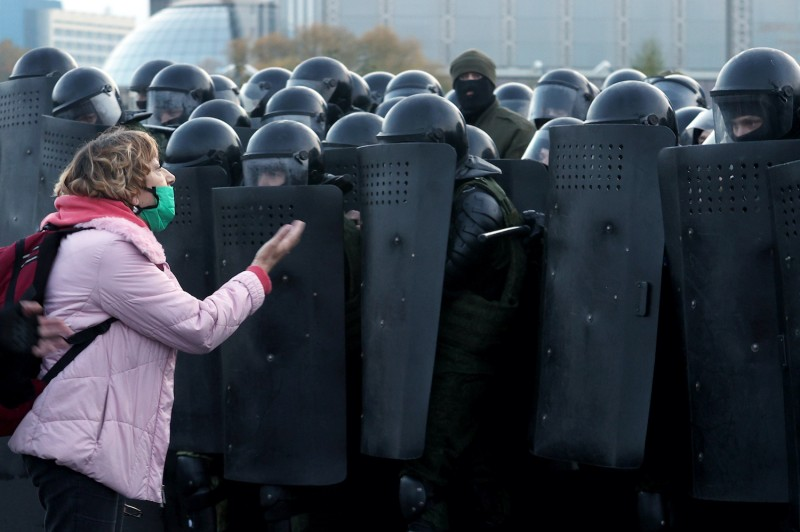 A woman argues with law enforcement officers during an opposition rally in Minsk, on October 25, 2020.