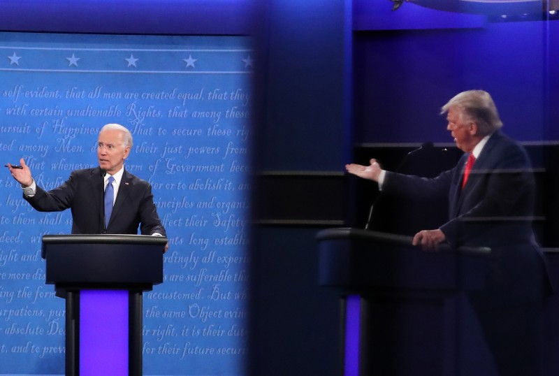 Democratic presidential nominee Joe Biden and U.S. President Donald Trump, shown in a reflection, participate in the final presidential debate at Belmont University in Nashville, Tennessee, on Oct. 22.