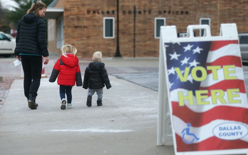 A voter departs with two children after casting her ballot during early voting in the 2020 presidential election on October 29, 2020 in Adel, Iowa.
