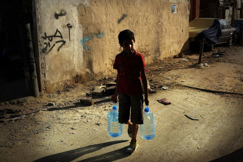 A boy walks with jugs of water in a poor neighborhood with a high concentration of Syrian refugees on June 27, 2013 in Beirut, Lebanon.