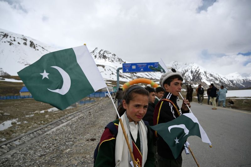 Young Pakistani youths hold national flags during a cycling competition near the Pakistan-China border on June 30, 2019.