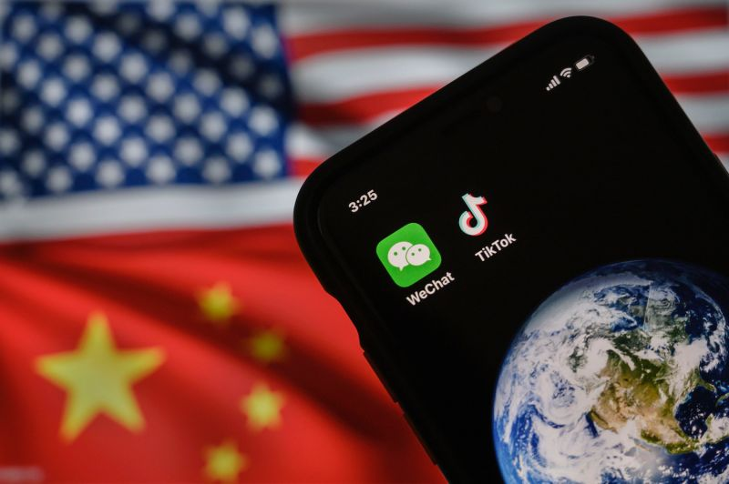 In this photo illustration, a mobile phone displays the logos for the Chinese apps WeChat and TikTok in front of a monitor showing the flags of the United States and China in Beijing on Sept. 22.