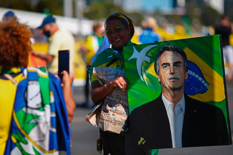A woman poses for a snapshot holding a portrait of Brazilian President Jair Bolsonaro during a demonstration in his support in Brasília on June 21.