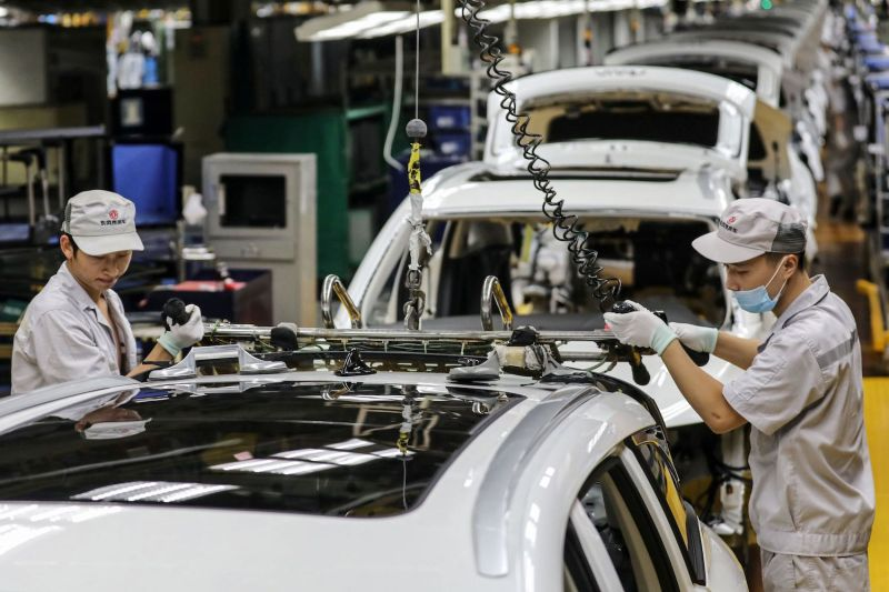 This photo taken on September 14, 2020 shows employees work on a car assembly line at a Dongfeng factory in Wuhan on Sept. 14.