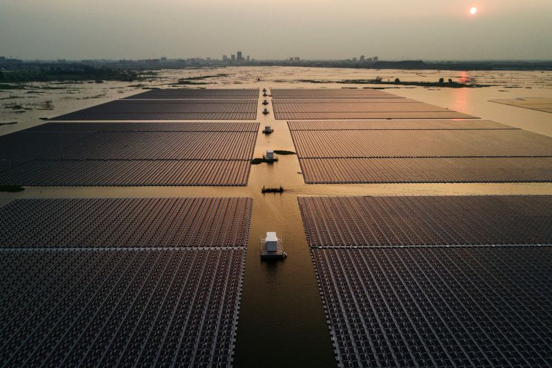 Chinese workers ride a boat through a large floating solar farm project in Anhui province on June 13, 2017.