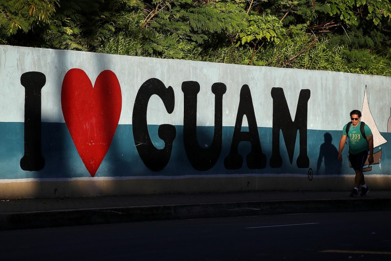 "A pedestrian walks by a mural that says ""I Love Guam"" in Tamuning, Guam, on Aug. 14, 2017."