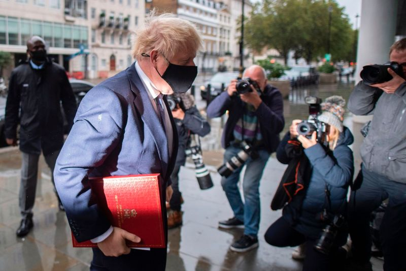 British Prime Minister Boris Johnson wears a protective face covering as he arrives at the BBC in central London on Oct. 4.