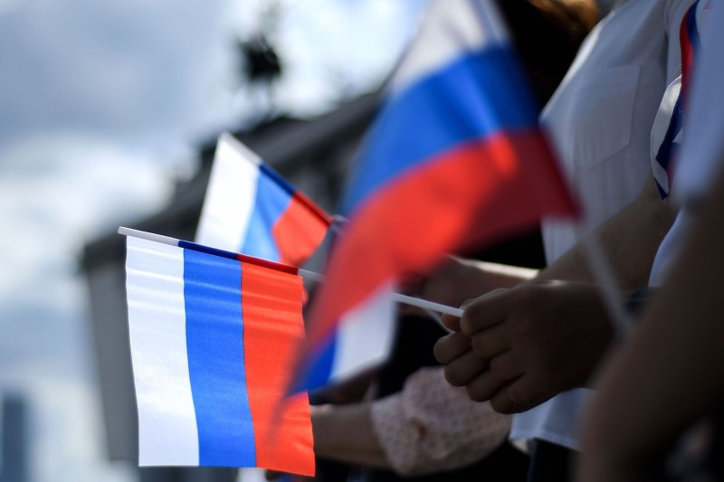 People hold Russian national flags during a celebration ceremony of National Flag Day at Poklonnaya Hill in Moscow on Aug. 22.