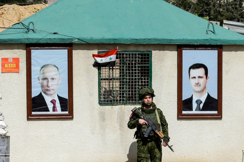 A member of the Russian military police stands guard between portraits of Syrian President Bashar al-Assad and Russian President Vladimir Putin at a guard post on the outskirts of Damascus, Syria, on March 1, 2018.