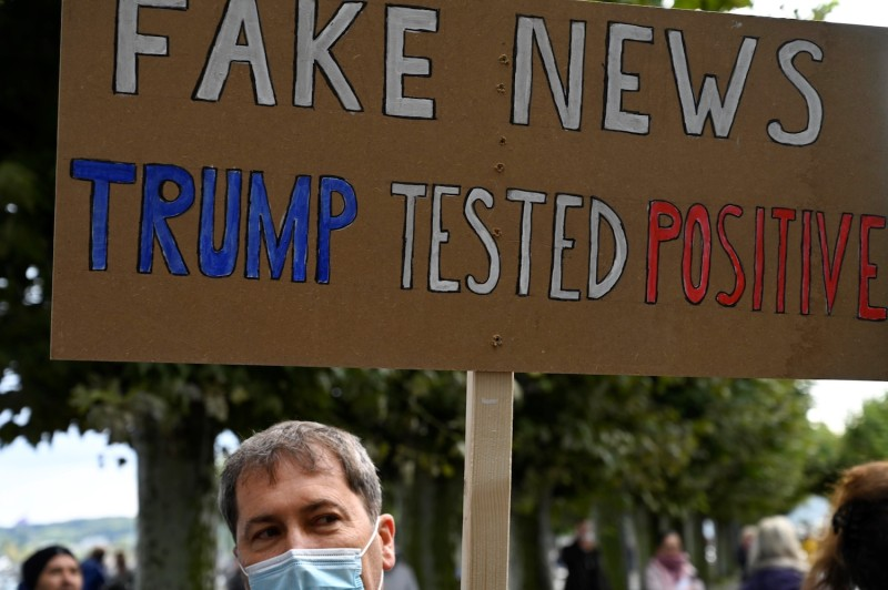 "A demonstrator holds up a placard reading ""Fake News: Trump Tested Positive"" in Konstanz, Germany, on Oct. 3, 2020."