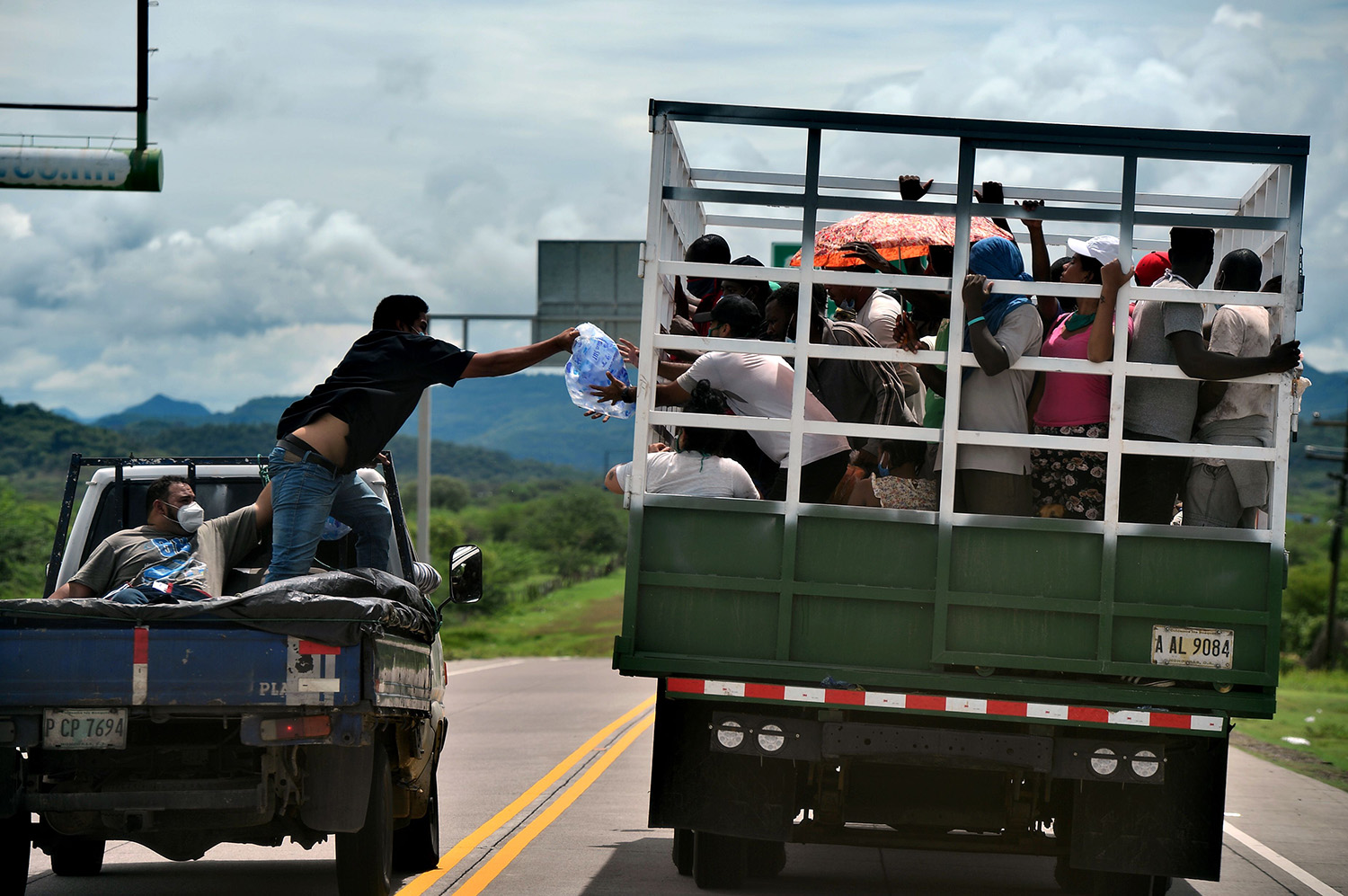 A man gives water to migrants heading to the border with Guatemala as they travel aboard a truck in Cerro de Hula on June 3. Nearly 100 migrants from Congo, Ghana, Ivory Coast, Haiti, and Cuba headed in a caravan from Choluteca, Honduras, to Mexico were stopped by the police for sanitary controls amid the coronavirus pandemic.