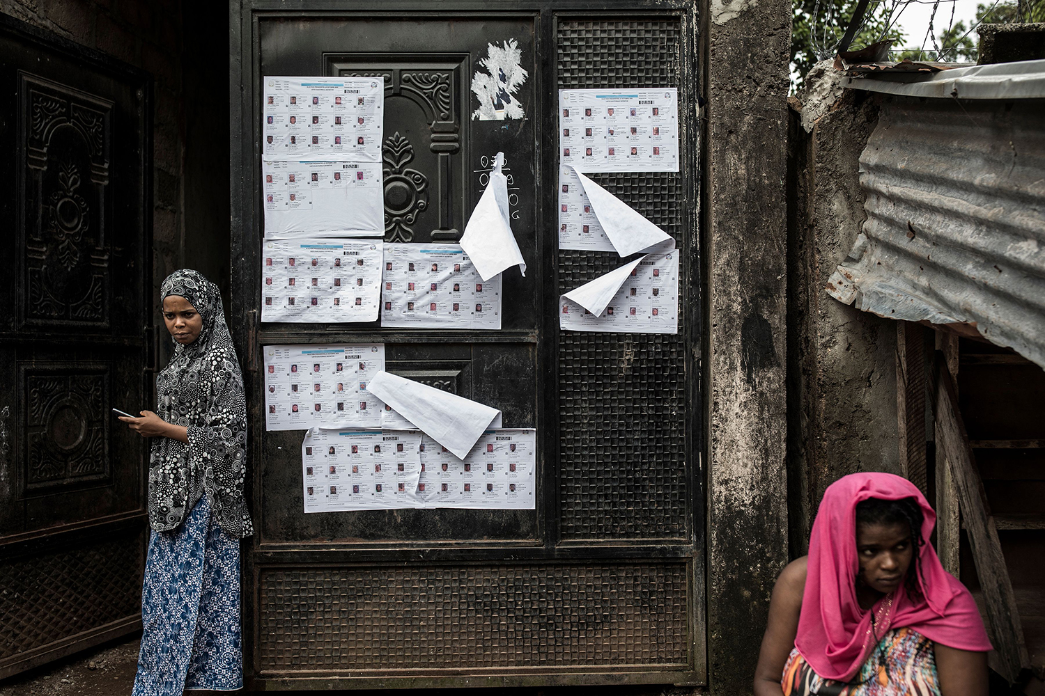 Women sit near candidate lists posted on a door during presidential elections in Conakry, Guinea, on Oct. 18. Guineans began voting slightly ahead of schedule in the first high-risk round of an election that marks the start of a busy electoral cycle in West Africa. JOHN WESSELS/AFP via Getty Images