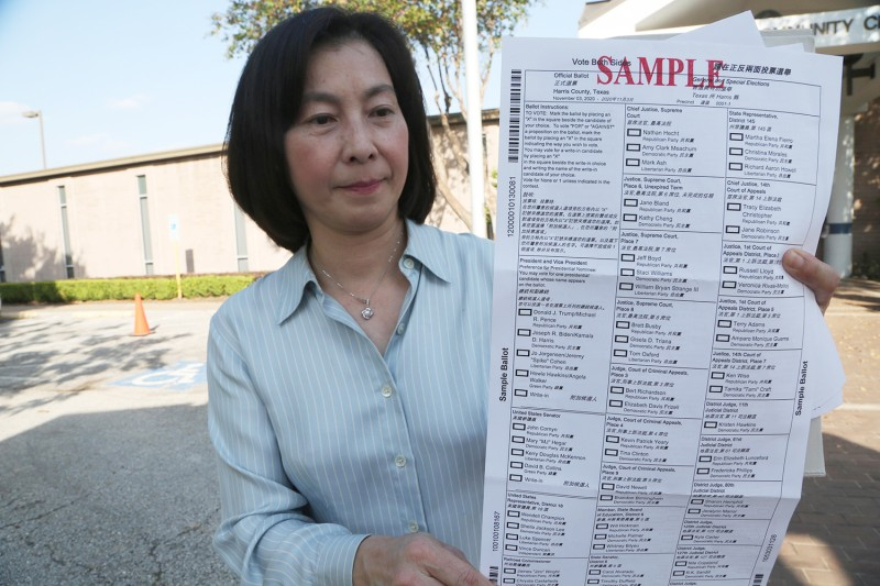 A woman presents a Chinese-language sample ballot for the 2020 presidential election at a polling station near the Chinatown area of Houston, Texas, on Oct. 14.