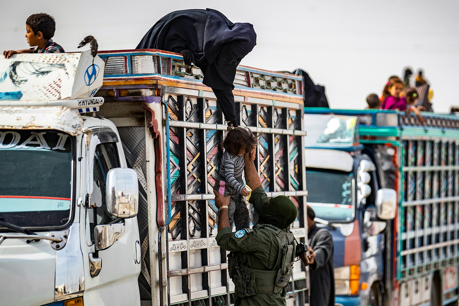 A Kurdish fighter helps a Syrian child board a truck at the Kurdish-run al-Hol camp in northeast Syria. The truck was transporting Syrian women and children suspected of being related to the Islamic State from the camp to their homes Oct. 28. DELIL SOULEIMAN/AFP via Getty Images