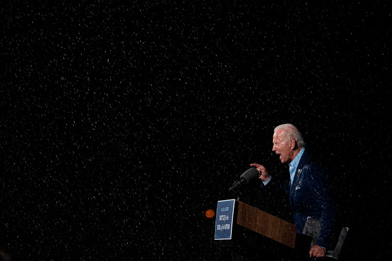 Former vice president and Democratic presidential nominee Joe Biden delivers remarks in the pouring rain during a drive-in event in Tampa, Florida, on Oct. 29. JIM WATSON/AFP via Getty Images