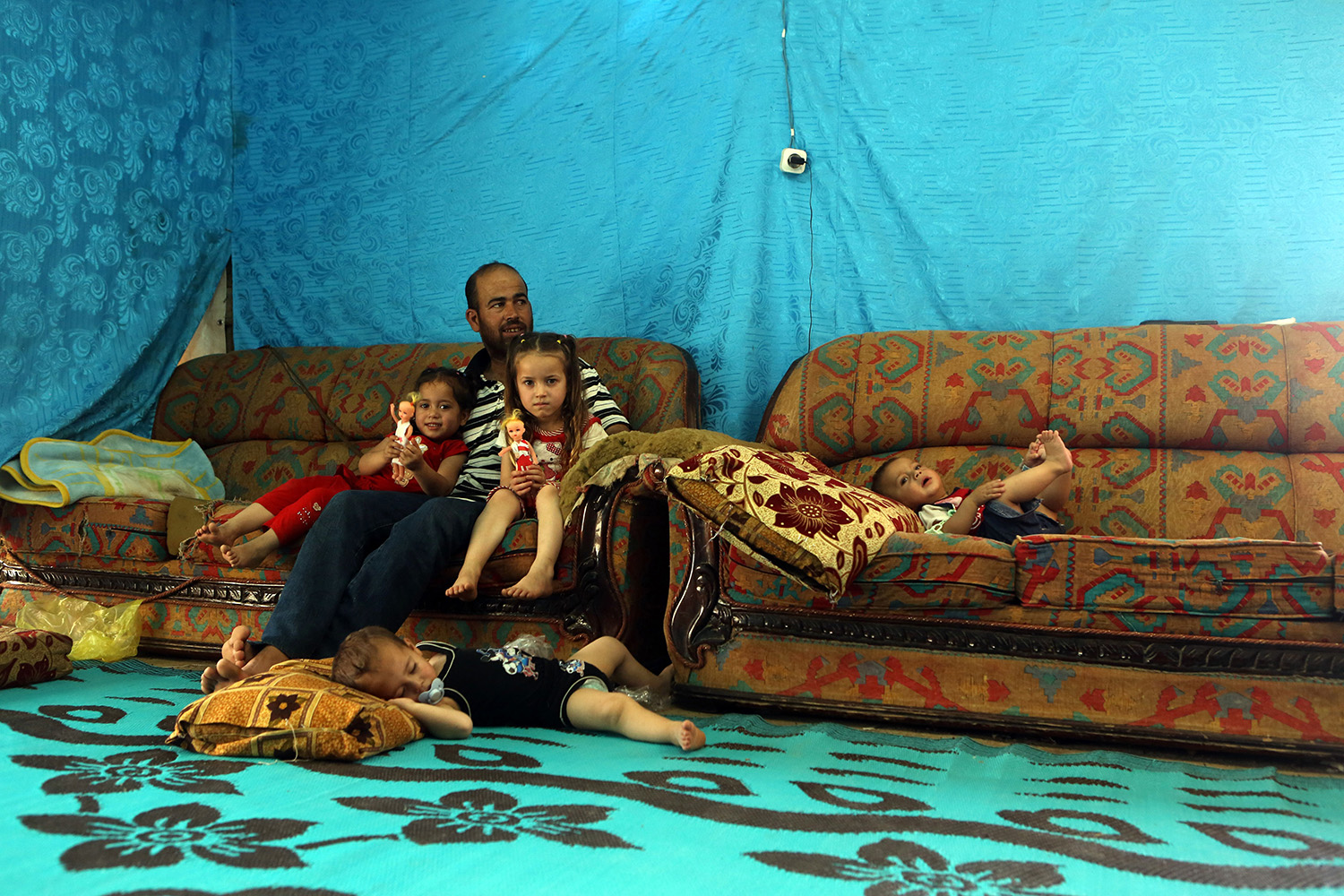 A Syrian refugee from Aleppo sits with his children in a makeshift tent in a camp in the town of Kab Elias in Lebanon's Bekaa Valley on June 20, 2016.