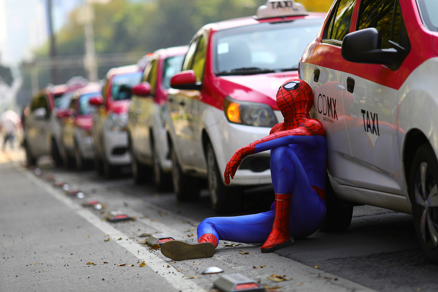 A person dressed as Spider-Man sits next to a line of cabs as taxi drivers protest against car-hailing apps such as Uber at the Angel of Independence monument in Mexico City on Oct. 12. Edgard Garrido/REUTERS