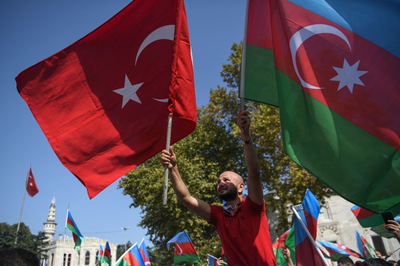 An Azeri protester waves the Turkish and Azerbaijani flags at a demonstration in Istanbul in support of Azerbaijan on Oct. 4.