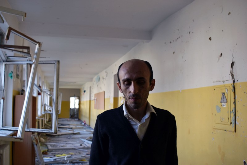 Artak Beglaryan, the elected human rights ombudsman for the Republic of Artsakh, stands in the wreckage of a Stepanakert school in Nagorno-Karabakh on Oct. 23. He was blinded by a land mine in 1995 and now works to document the ongoing conflict with Azerbaijan.