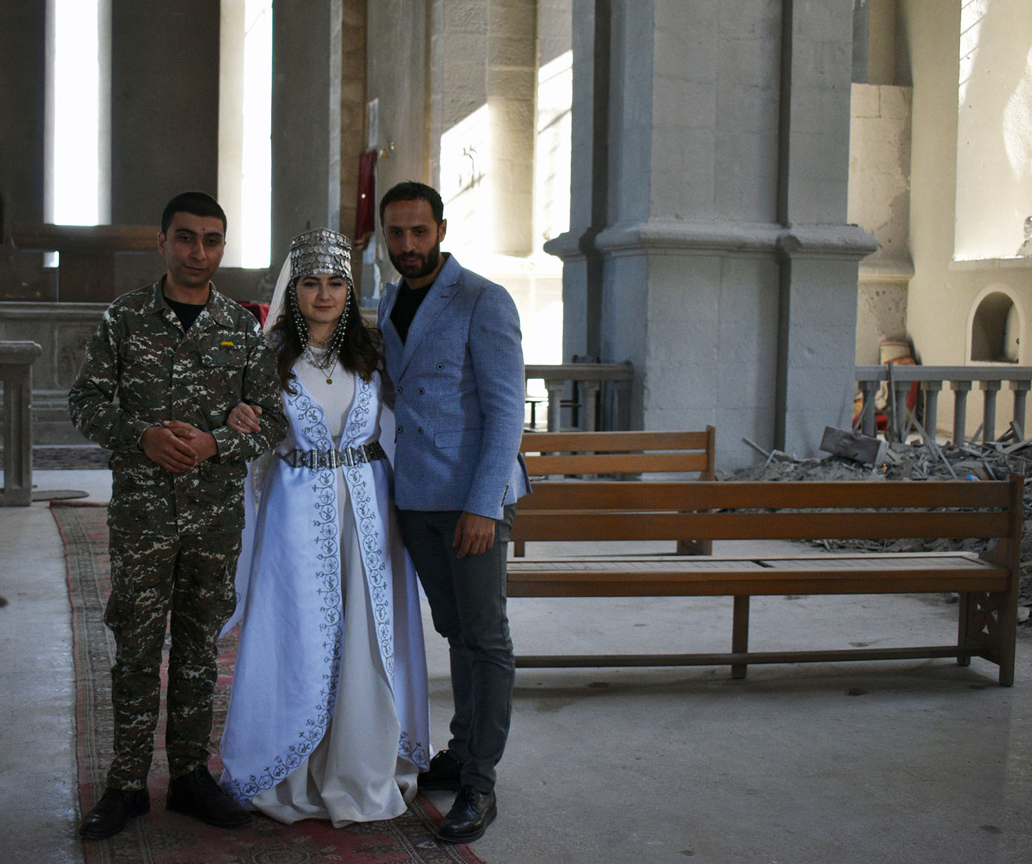A journalist poses with an Armenian couple who married in an act of defiance at a church in Shushi, Nagorno-Karabakh, on Oct. 23.