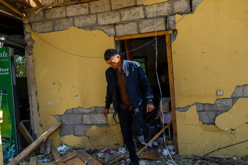 A local resident walks in front of a damaged building in Barda, Azerbaijan, near the disputed Nagorno-Karabakh province's capital Stepanakert, on October 9, 2020, as Azerbaijan and Armenia hold their first high-level talks after nearly two weeks of clashes.