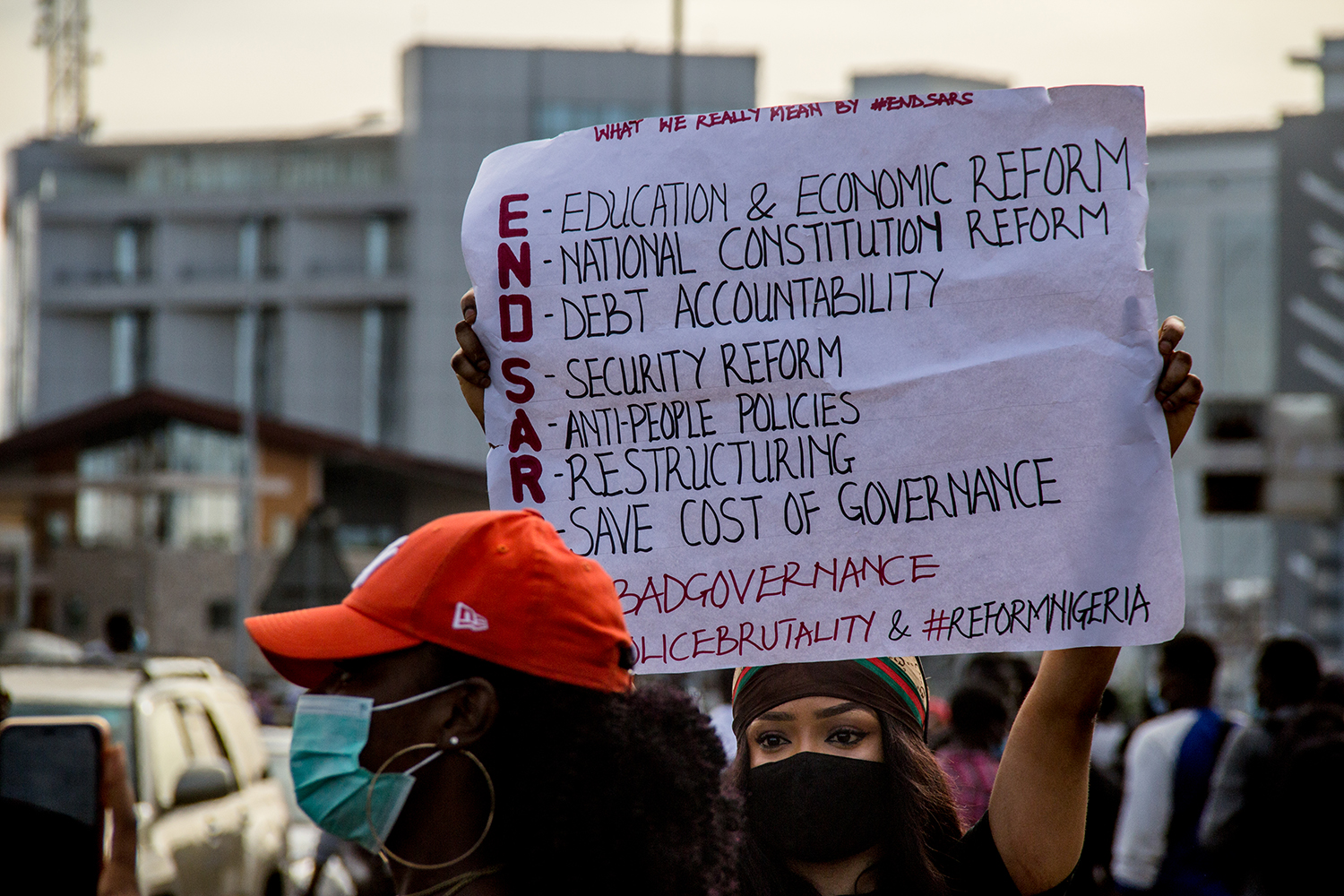 A woman holds a sign during a protest at the entrance to the Lekki Toll Plaza on Oct. 18.