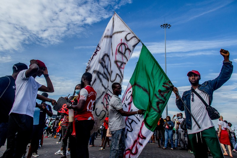 "A protester poses with a banner reading ""End SARS"" at the Lekki Toll Plaza in Lagos, Nigeria, on Oct. 18."