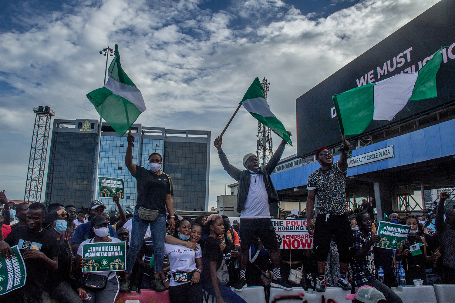 "Protesters fly the Nigerian flag chanting ""Soro soke,"" a Yoruba phrase that translates to ""Speak up"" in English, in Lagos on Oct. 18."